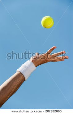 Serving ball. Close-up of male hand in wristband throwing tennis ball against blue sky - stock photo