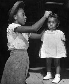 Mother grooming her daughter for healthiest-baby contest held at all African American fair. Memphis, TN, 1941. Photographer Alfred Eisenstaedt.