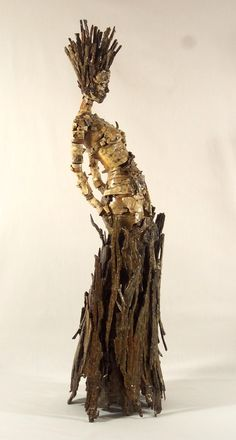 """Becky Grismer, New Skin. New Skin is part of a series of tree bark figures that are meant to represent some of the individual characteristics shared by trees and humans. New Skin represents the common characteristic of both trees and humans naturally exfoliating their skin. The sculpture is made entirely from birch and hickory shag bark. Both are trees that naturally shed their bark or """"skin""""."""