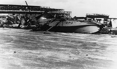 "Aircraft wreckage and a badly damaged hangar at Naval Air Station Kaneohe Bay, Oahu, shortly after the Japanese air attack. The plane in the foreground is a consolidated PBY Catalina of Patrol Squadron 12, marked ""12-P-3"".  When the PBY and Kaneohe Bay was attacked, eighteen sailors and two civilians were killed. Sixty-nine others at the base were injured."
