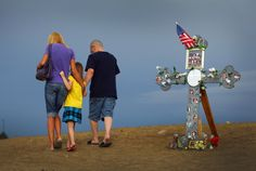The 40 Pictures Of 2012 You Won't Forget. Aurora Shooting  A family walks past a cross adorned with photographs of victims of the mass shooting at the Century 16 movie theatre on July 30, 2012 in Aurora Colorado.