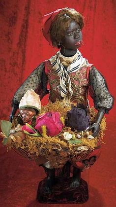 """All-Original French Musical Automaton """"Flower-Seller with Surprises"""" by Gustav Vichy 25"""" (64 cm.) A beautiful black-complexioned papier-mache lady with brown glass eyes,mohair lashes,painted brows,open mouth with two rows of teeth,dark mohair wig arranged under turban,carton torso and legs with bare feet,defined toes,wire upper arms,papier-mache hands,wearing her original elaborate silk and brocade costume"""