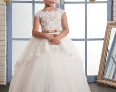 This gorgeous flower girl dress is inspired by the class and beauty of the Audrey Hepburn era. Layered tulle give this dress a timeless look with a corset back that laces up for just the right fit. Sheer lace covers the neckline and a lace overlay on the skirt brings the class and elegance to this dress. Your choice color of sash. Your childs EXACT measurements are a must for perfect fitting. This is a CUSTOM flower girls dress made especially for your gorgeous little one for that special…