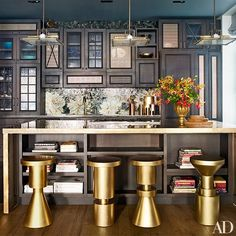 Pendant lights by Early Electrics are suspended above a bronze-clad island in the kitchen, where cabinetry designed by Don Stewart meets a custom-made backsplash by Mosaic Sphere Studio   archdigest.com