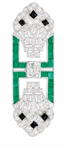 An Art Deco Diamond, Emerald and Onyx Brooch, circa 1920 The openwork plaque with twin topiary motifs centering an Asscher-cut diamond weighing approximately 2.10 carats, rectangular emerald trim amid diamond-set jardiniere terminals accented by black onyx, mounted in platinum, French assay marks