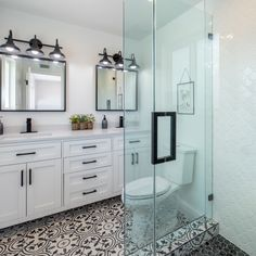 We adore the contrast the vanity hardware, mirrors, lighting, and floor tile provide this otherwise all-white bathroom.  #vanitylight #vanitylighting #vanitylightedmirror #doublesinkvanity #doublesinkbathroom #doublesink #doublesinkvanityunit #interiorstyling #bathroomvanity #bathroomvanitytops #homedecorideas #bathroomdesign #homedesignideas #interiorandhome #bathroomvanityideas #interiordesignlovers #designdetails #interiordesignjunkie #bathroomvanityunit #bathroomdesignideas #vanityroom Black And White Bathroom Floor, Black White Bathrooms, White Bathroom Decor, White Vanity Bathroom, Bathroom Floor Tiles, Bathroom Interior Design, Bathroom Mirrors, Classic White Bathrooms, Paint Bathroom