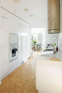 Keittiön ikkunaseinällä on vain alakaapit ja Lapetekin lasihyllyt. Vastakkaisella seinällä on korkeat kaapit lattiasta kattoon. Jääkaappi ja pakastin on integroitu ja mikro piilotettu rulo-oven taakse uunin yläpuolelle.