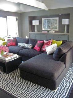 Charcoal Gray sofa on top of bold patterned rug, gray tones with a pop of color