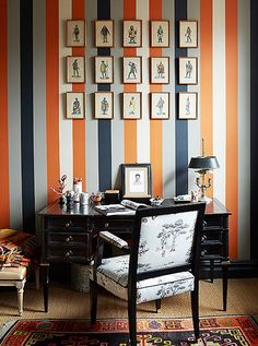 Vertical striped wallpaper makes a bold and inspiring statement in any home office.