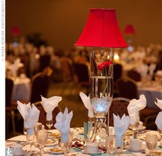 For the taller centerpieces at their reception, Krista and Jake rented crystal vases from the convention center and topped them with red, silk lampshades. Each one was filled with water, glass marbles, water-activated LED lights, and a single ruby gerbera...