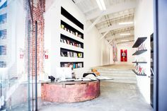Modern and colorful art gallery with industrial glass and metal finishes, white walls, white ceilings and concrete floors with chic and comfortable furniture.