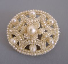 GEORGIAN/early VICTORIAN natural seed pearl  brooch with gut on mother-of-pear backing set in gold filled setting, circa  1840, 1-1/2 by 1-1/4. This delicate piece is not missing a single tiny pearl  and is in amazing condition, a great example of the hand work that makes these  so desirable.                  It is interesting that seed pearls were used in different ways as the  decades progressed. In Victorian jewelry it was set in gold, onyx and jet,  where the seed pearls were often…