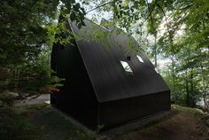 Jean Verville creates a black cottage in a Quebec forest