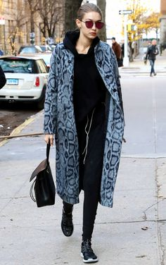 Gigi Hadid in a snakeskin-print coat, black sweatsuit, Mansur Gavriel bag and sneakers - click ahead for more celebrity winter outfit ideas