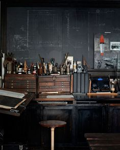 The slate walls, drafting table and old tool boxes are a great mix.  A great work/project room.