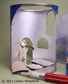 Openings are cut in a cardboard food container to make a house for a miniature felt mouse.