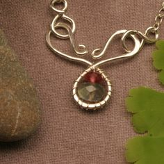 Eye catching wearable art... be prepared for compliments!      Red and Green Tourmaline beads surrounded by sterling silver.      Notice this handcrafted pendant is also the necklace clasp...classic j