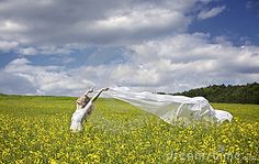Young happy woman standing in yellow rapeseed field holding a white long piece of cloth in the wind expressing freedom.