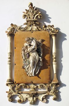 Description:Vintage wall applique having porcelain figural group on leather board around foliate carved frame.  Material:Wood, porcelain  Dimension: 16(W) 32(H) 2(D)  Location:MCT  Quantity:1  Status:avail  Price:Call for Price  Price Type:single