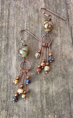 "Unique handmade earrings! Copper dangles with boho glass beads hang from a red creek jasper bead. Very light weight and rich in earth tones. Approx 1.5"" in length."
