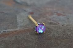 "Purple opal gold nose ring. Tiny gold nose stud with a 2mm prong set purple opal gem. 20 gauge nose ring, 1/4"" long post, made of 316L surgical steel plated gold with a tiny synthetic purple opal ston"