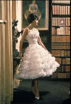1960 Model is wearing a frothy, tiered party dress by Chanel,