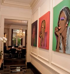 The long hallway from the front door leads into the dining room and is lined with Andy Warhol's portraits of drag queens.