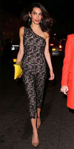 Clooney shed her daytime professionalism and hit the town (the Electric House private members club, to be exact) with designer Stella McCartney. For the occasion, Clooney slipped on a sexy one-shoulder lace Stella McCartney jumpsuit that she expertly styled with statement earrings, a python-yellow envelope clutch, and nude pointy-toe pumps.