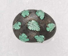 RENÉ BOIVIN An Emerald and Bronze Ring, circa 2005 The wide tapering bronze mount with silver patina enhanced with seven carved emeralds of foliate motif. Signed 'René Boivin' numbered 1/1 and dated. With French assay marks