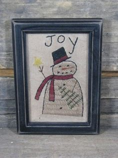 A primitive country snowman with JOY stitched is on this framed Christmas sampler available at Primitive Star Quilt Shop.
