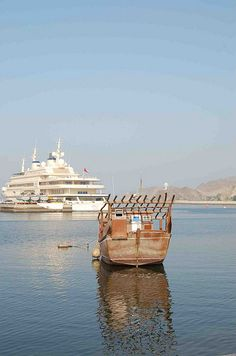 Muscat, Oman - Sultan's Yacht in background and dhow in front. Old and new!