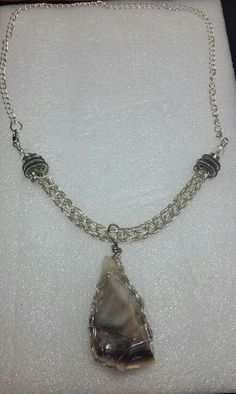 Silver viking knit necklace with titanium end caps and viking knit wrapped silver opalized wood pendant.