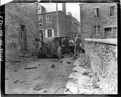 Tessy-sur-Vire, 3 août 1944, un soldat américain de la 35th division inspecte l'épave d'une chenillette et du canon Pak 40 qu'elle tractait.