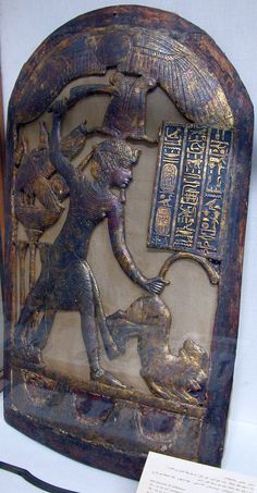 Egyptian ceremonial shield, from the tomb of Tutankhamun (pharaoh Tut) 1333-23 B.C., the king is holding a scimitar with his right hand, ready to slay two lions whose tails are grasped in his left hand.