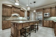 Updated kitchen // Brown wood cabinetry, light granite countertops, island with seating, stainless, diamond tile backsplash