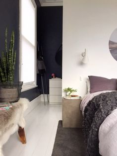 dark blue / black walls + white,  wall added behind bed
