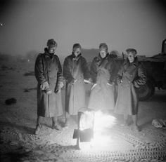 THE BRITISH ARMY IN NORTH AFRICA 1942. Soldiers in greatcoats warm themselves around a brazier, 11 July 1942. The temperature in the desert could fall considerably during the night.