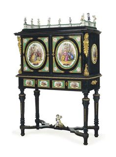 A GERMAN ORMOLU AND PORCELAIN-MOUNTED EBONY AND EBONISED CABINET-ON-STAND CIRCA 1860 The three-quarter galleried top surmounted by figures, above a pair of doors and two frieze drawers, mounted overall with porcelain plaques, the doors each with a central oval plaque decorated with a scène gallante, the interior fitted with one long and four short drawers to each side about a mirrored recess flanked to each side by two porcelain term figures, on turned stop-fluted tapering legs joined by a…
