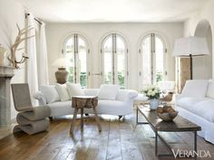 Modern neutrals dominate designer Pamela Pierce's French-style Houston home, like in this light-filled living room that mixes the old, the new, and the unexpected. Find the full tour here. Rolled-arm antique English sofa and 18th-c. iron candlestand floor lamp, W. Gardner, Ltd. Frank Gehry Wiggle Chair, Vitra. Tri-leg 19th-c. elm table, Area.    - Veranda.com