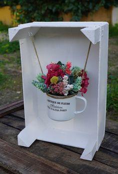 Flores secas, preservadasy artificiales (sólo las piñas verdes) en una taza que cuelga de una caja de frutas reciclada.  Medidas: 19,5 x 30 cm (caja incluida en el centro)  Se puede colgar en la pared a modo de cuadro o ponerlo sobre una superficie como en la foto. Las flores son duraderas y no requieren de ningún cuidado especial.  Si te gusta este columpio pero quieres hacer algún cambio, escríbenos a tienda@floresenelcolumpio.como ponlo en observaciones cuando hagas el pedido.