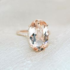 This stunning 6.10 ct. morganite and diamond engagement ring will sweep her off her feet. Bright and beautiful center stone is eye clean. Simple rose gold shank encrusted with diamonds. Huge, beautiful oval cut morganite grasped with claw prongs. Unique & breathtaking. Center Stone: