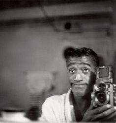 Sammy Davis Jr taking a self-portrait with a classic camera...