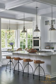 Custom white shaker style cabinetry, dark oak floors, carrara marble countertops, custom white leather banquette and Thermador appliances. Island has front and rear storage. Rustic bar stools juxtapose the white color scheme. Stephen Allen Photography
