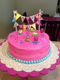 Shopkins DIY cake ; cake stand and birthday banner are from target, pink Pillsbury frosting, sprinkles and blue round candies from party works.