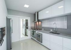 A cozinha recebeu mobiliário sob medida, executada em MDF branco diamante com portas em vidro branco e bancada em silestone cinza estelar. O material também cobre a parede principal. Em harmonia, persiana metalizada.