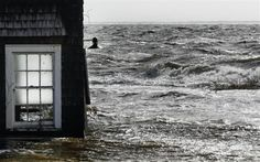 Water pushed up by Hurricane Sandy splashes into the window of a building standing by the shore in Bellport, New York