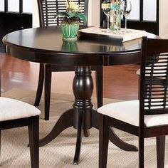 """Featuring a pedestal base and a rich cherry finish, this versatile wood dining table brims with timeless appeal.      Product: Dining table   Construction Material: Hardwood   Color: Cherry  Features:Pedestal base   Will enhance any décor Dimensions: 30"""" H  x 44"""" Diameter   Note: Chairs not included"""