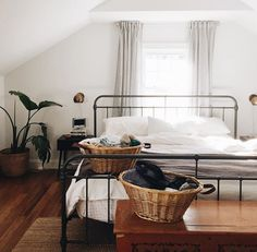Iron bedframe in attic bedroom. White walls, wood floor.