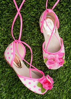 A traditional ballet flat style with a twist! These brightly colored lace-up flats have a hot pink and light cream polka dot pattern. They feature a flower trio in shades of pink with a peep toe detail. Comes with a matching clip!