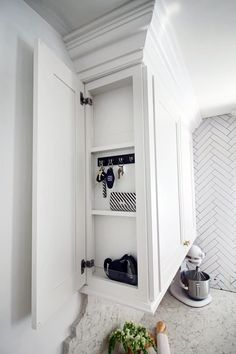 Add just a few more inches to your upper kitchen cabinets to stash away dog leashes, keys, wallets, notes, and beyond.